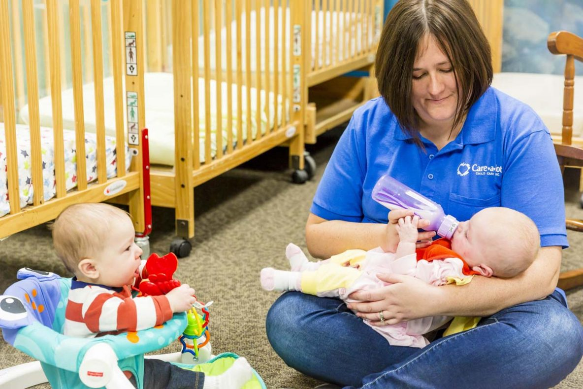 "Care A Lot ""Care"" giver, bottle-feeding an infant"