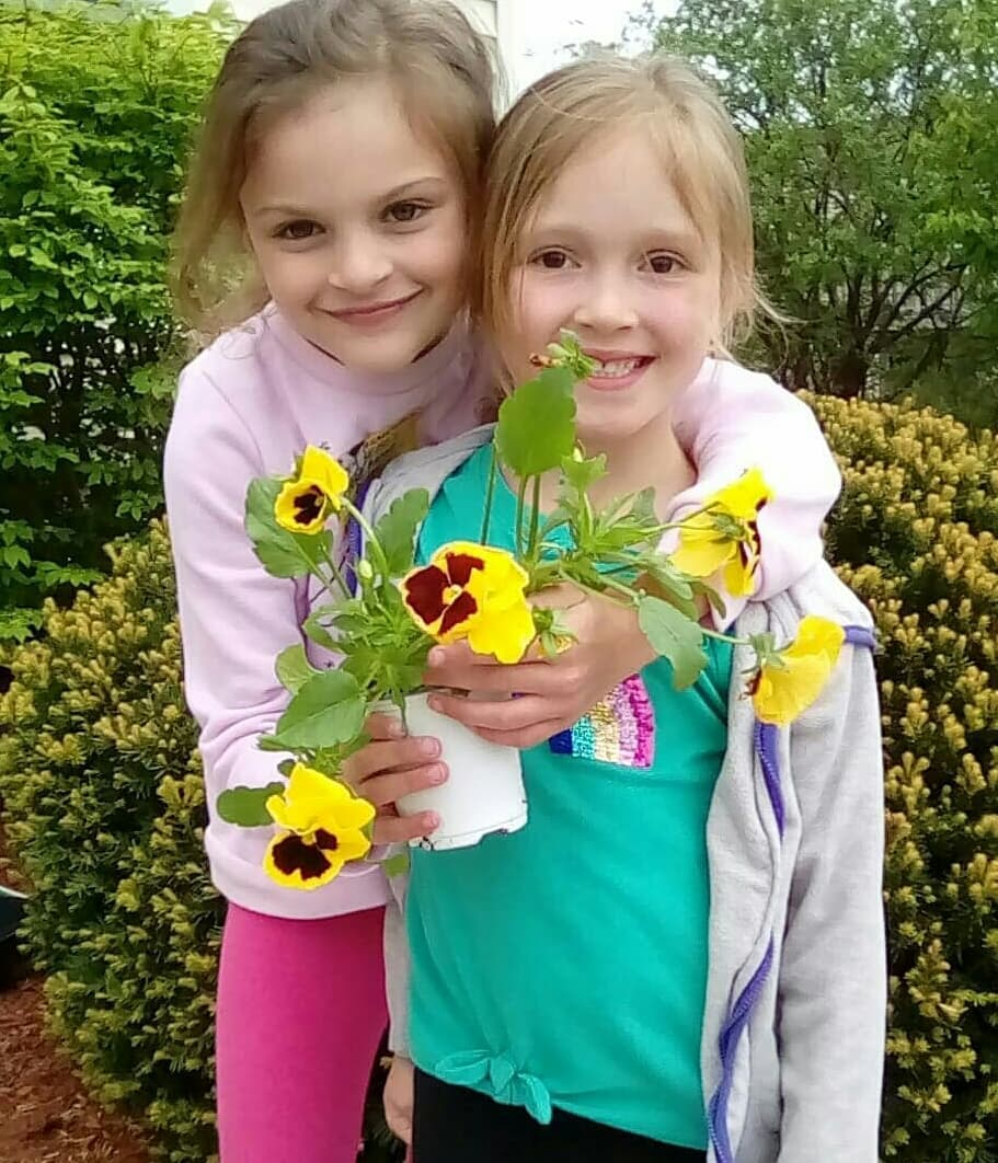Two young girls holding a potted flower at Care A Lot Child Care Center