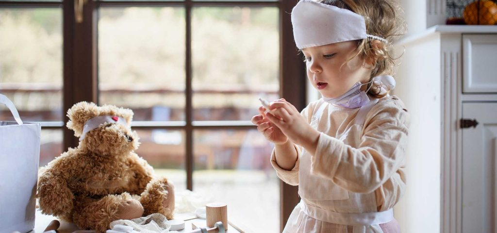 boy dressed as a doctor with his teddy bear
